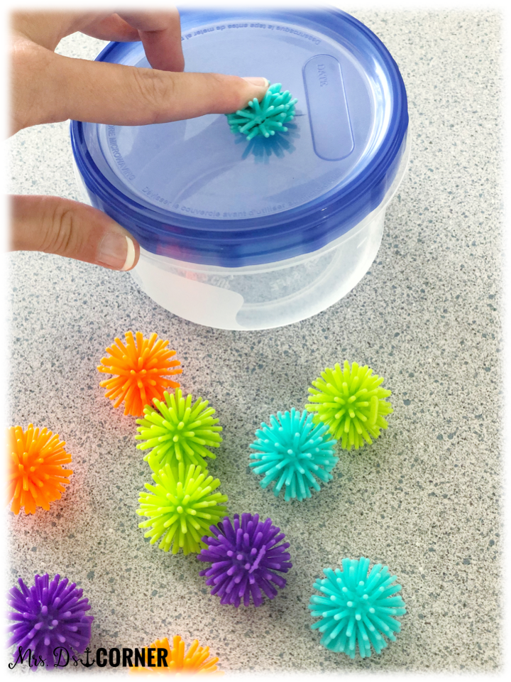 "Put the spike balls inside of the container one at a time. Students say or use their AAC device to say ""put in""."